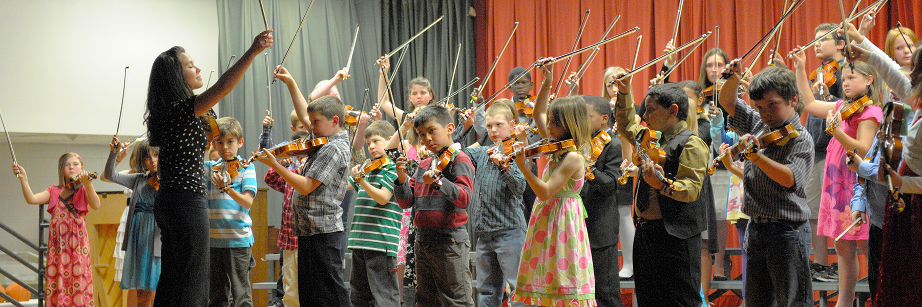 Image of IU Jacobs Music Education student leading a group of elementary school violin students.